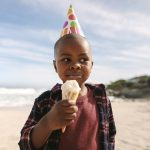 African boy wearing party hat eating ice cream cone on the beach. Birthday boy having ice cream in the sea shore.